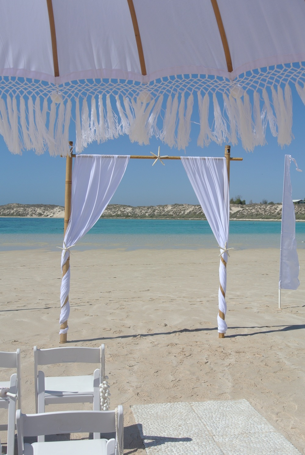 White Bohemian Umbrellas, Pebble Matting, Bamboo Arch With White drapes and Starfish