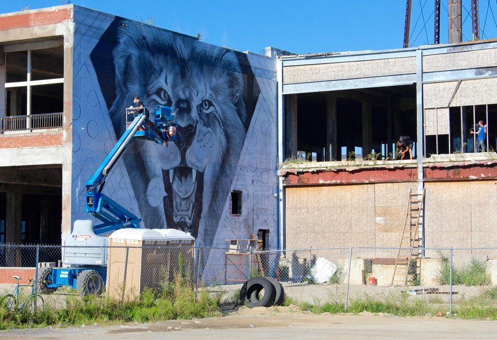 Artist Greg Mike working on his wall,accompanied by an audience