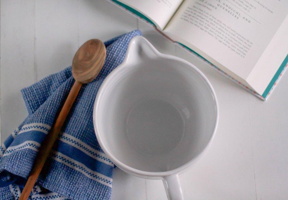 batter bowl  ,   olive wood spoon  ,   dishtowel  ,   cook book  .