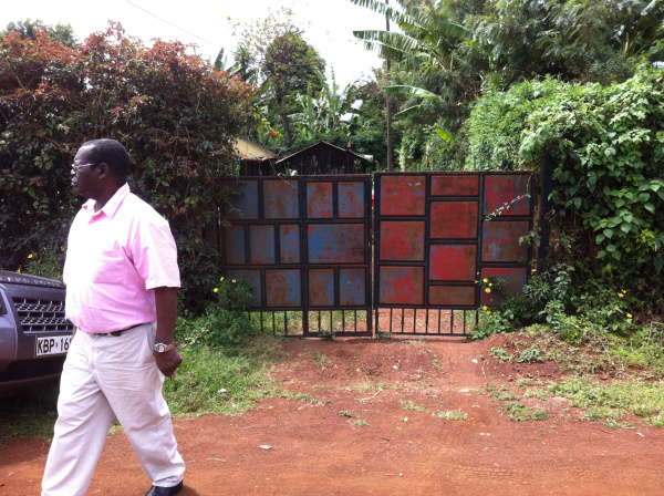 Peter Kanyoni in front of the gate for the land that he is letting us use.
