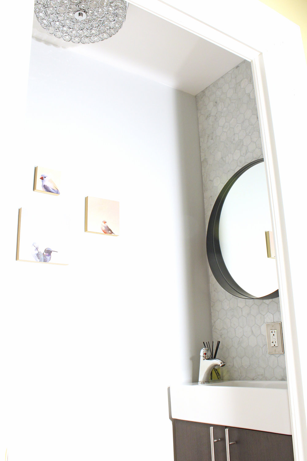 A small powder room makeover with marble hex tile and round mirror over a small, narrow vanity.