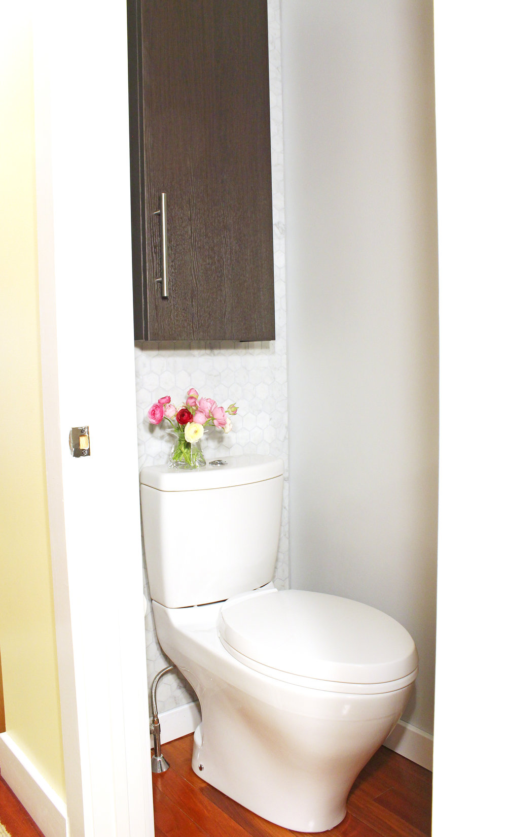 A small powder room makeover with marble hex tile and modern toilet.