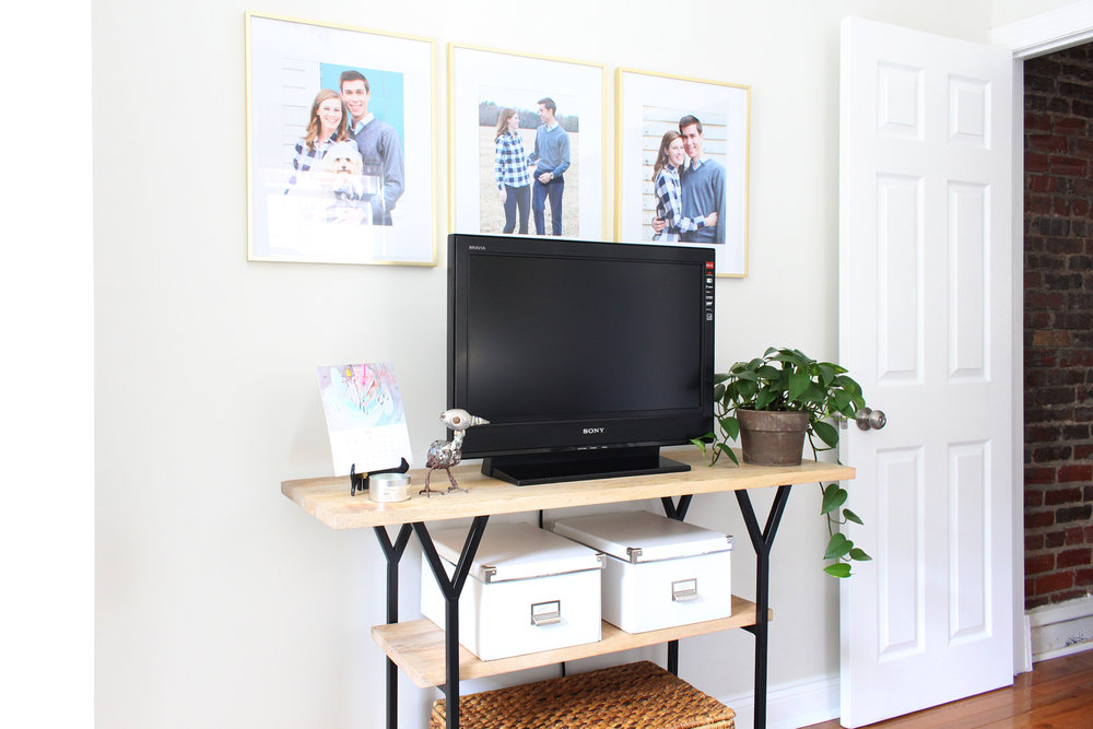 TV console styled with framed photos, a pretty green plant, and small storage boxes.