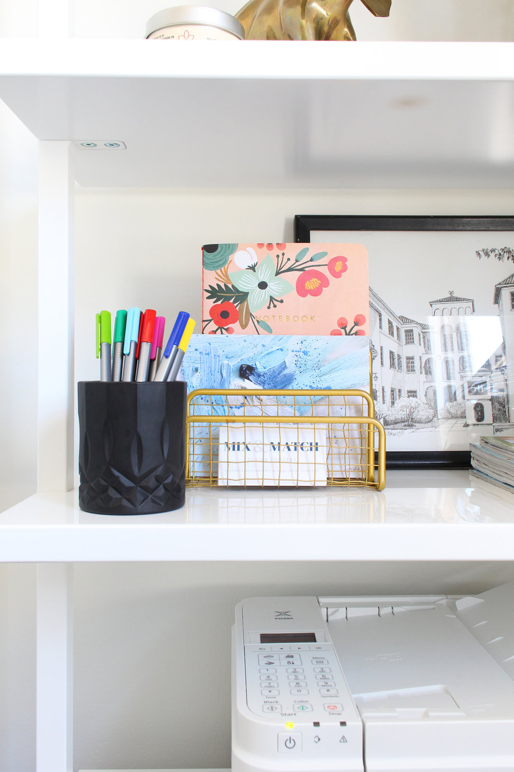 Office essentials and pretty pieces on bookshelf.