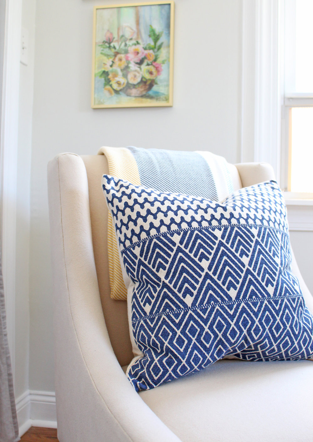 A modern and bright home office gets a bohemian touch in the form of a blue throw pillow.