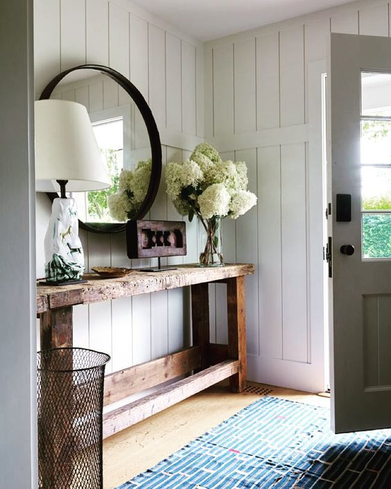 Farmhouse style entryway in the Hamptons with a beautiful console + mirror combination.