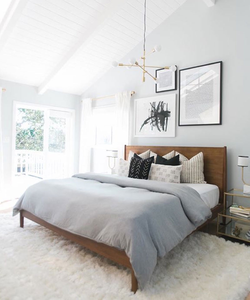 How to decorate around a bed. Option: hang an eclectic collection of art on the wall above the bed. (Design: West Elm) // mid-century bedroom, eclectic bedroom, neutral bedroom, mudcloth pillows