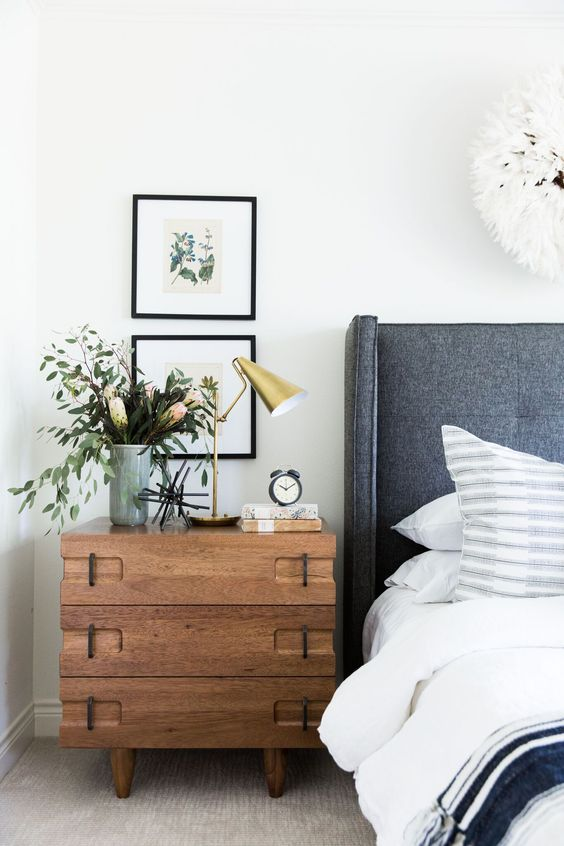 How to decorate around a bed. Option: hang stacked art above a nightstand (Design: Studio McGee). // coastal modern bedroom, gray headboard, three drawer chest nightstand