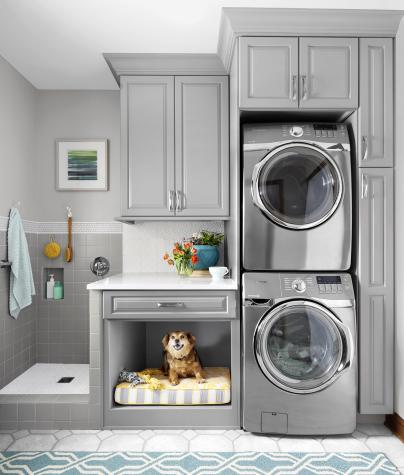 Multifunctional laundry room with gray cabinets and a dog area.