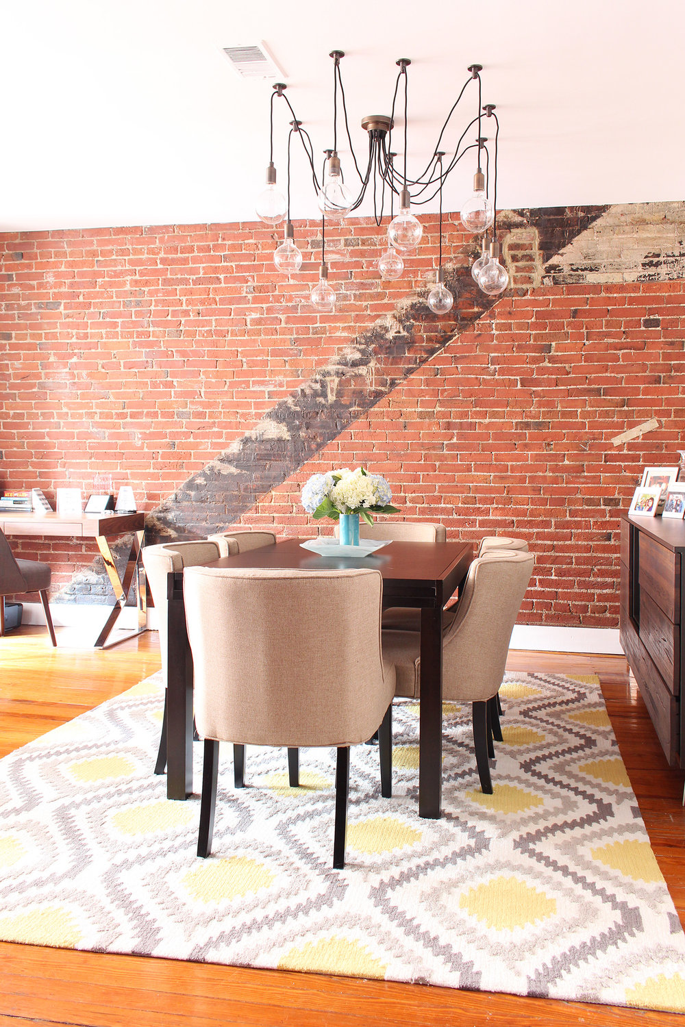 Contemporary meets classic in this converted textile factory condo's dining room // contemporary dining room, transitional dining room, exposed brick