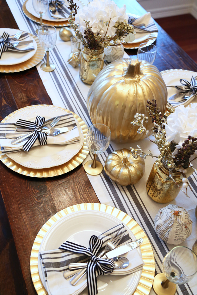 Black and gold tablescape inspiration for your Thanksgiving table. Use gold chargers, a black and white table runner, and other black and gold touches to complete the look. Want more Thanksgiving table decor ideas? Head to this post!