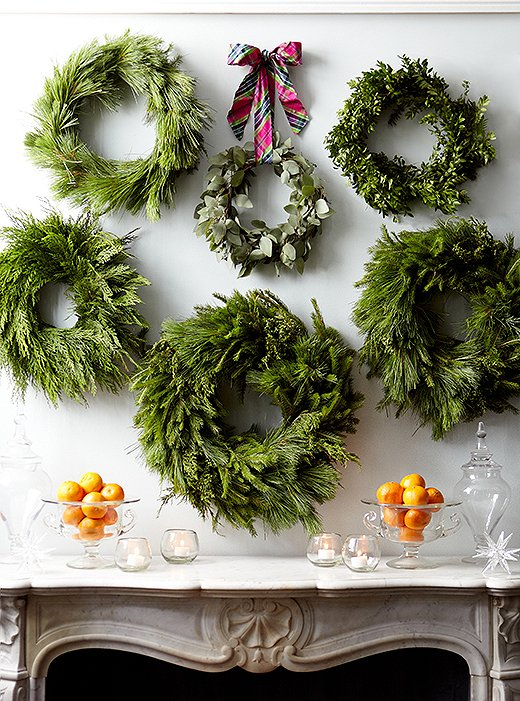 Cluster several wreaths together above a fireplace or on a wall for a big impact when you decorate your home this holiday season. // Christmas wreaths, creative Christmas decor, creative holiday decor ideas, simple holiday decorating