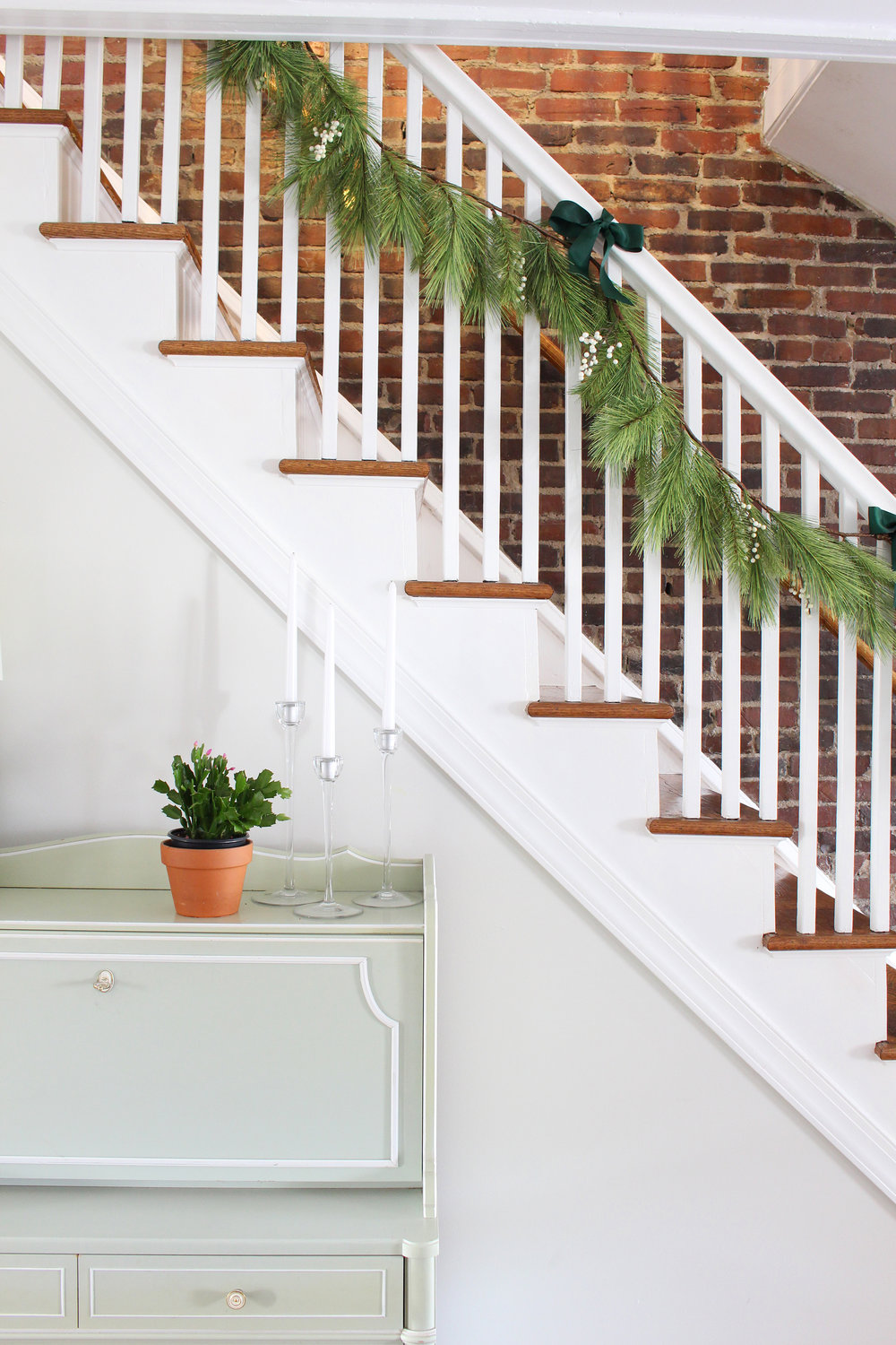 Adding greenery to your home in the form of a pine, cedar, or mixed garland is one of the most impactful ways to decorate for the holidays, and it's also one of the simplest and quickest! // hang garland, how to hang greenery, Christmas garland, artificial garland on railing, hang garland on stairs