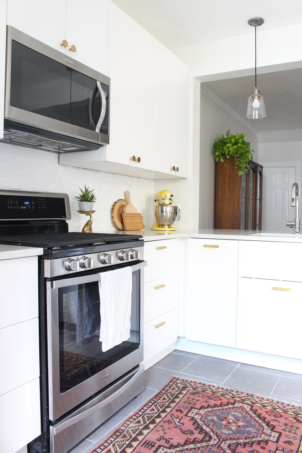 White modern IKEA kitchen, budget-friendly kitchen renovation, vintage rug in kitchen