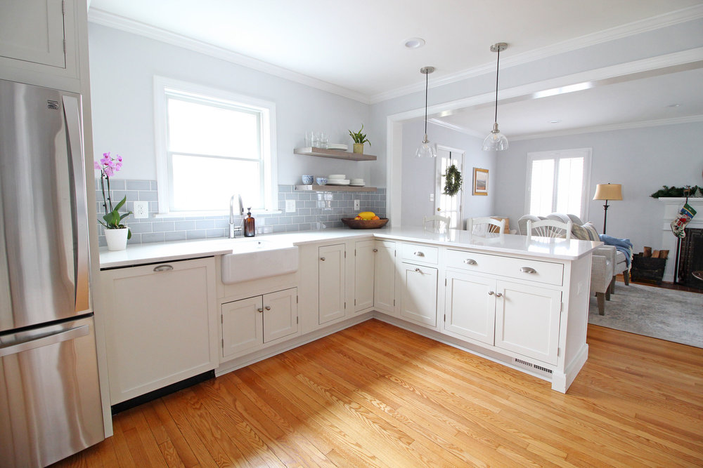 A stunning transitional farmhouse style white kitchen with inset cabinets opens up to the living room in this Virginia home. Open shelving is functional and stylish. You won't believe what this looked like before!