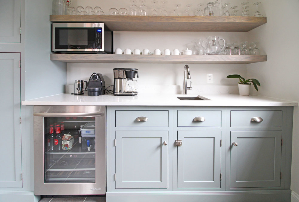 Light, blue-green cabinets in this transitional farmhouse butler's pantry perfectly complement the blue glass subway tile in the neighboring kitchen. Open shelving provides great storage without the weight of upper cabinets, and a beverage fridge and small sink add functionality.