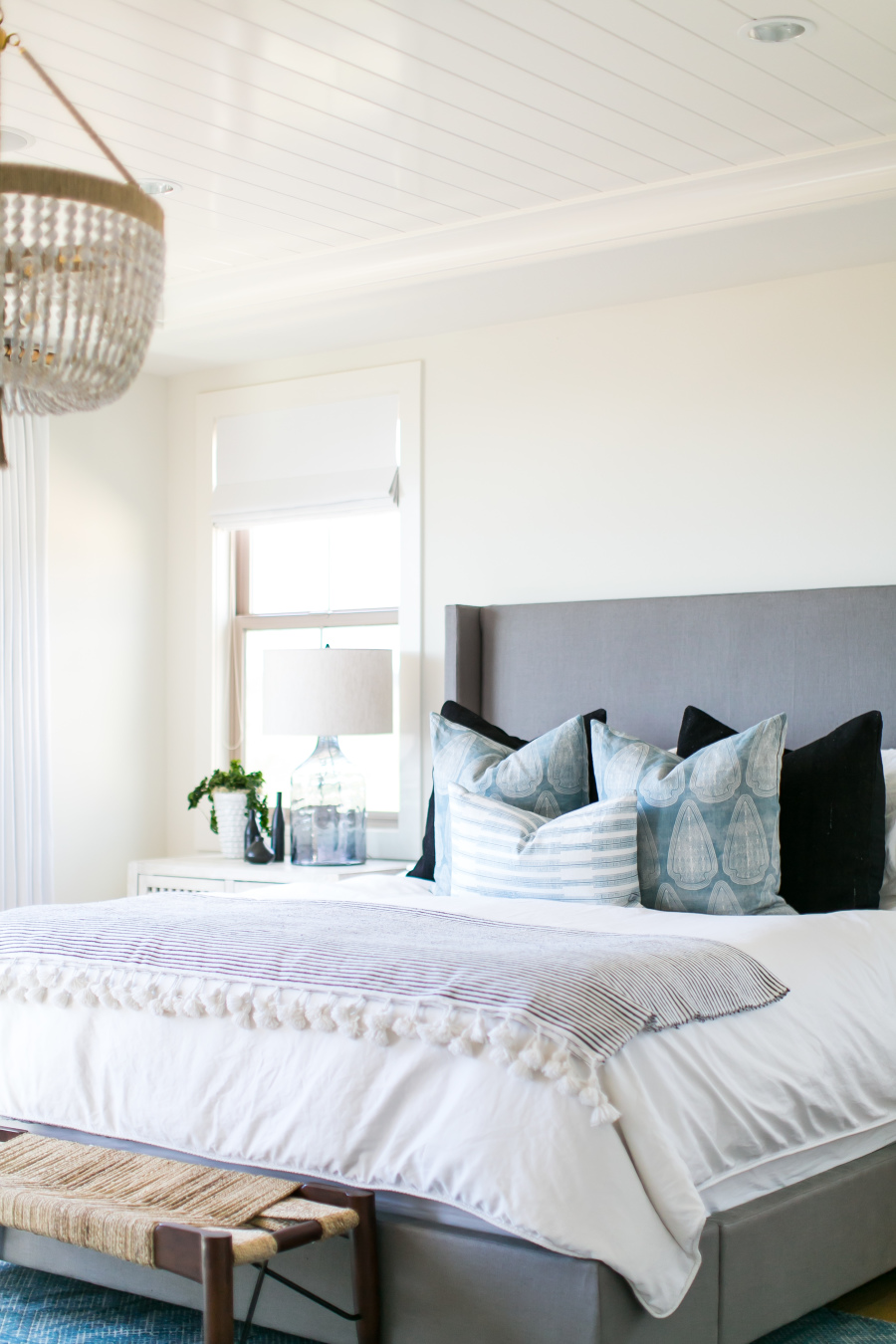Get the look of this fresh feeling blue and white coastal style bedroom on the blog! I'm loving the simple look of this bedroom with its upholstered wingback headboard and blue pillows.