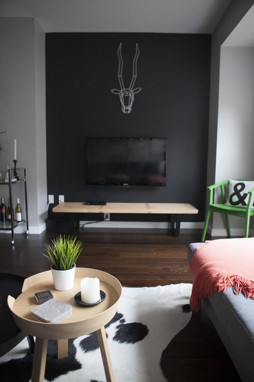 How to decorate around a TV. Hide it by painting the wall behind it a dark color. Come see other ideas and inspiration in this blog post!