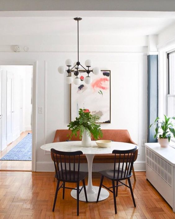Get the look of these cozy, small, and modern breakfast nooks over on the blog! This beautiful example has a marble topped pedestal table, leather bench, and black dining chairs. I love the abstract art and mid-century modern light fixture too!