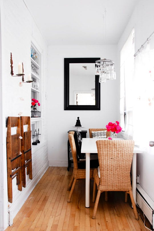 Carve out a dining area in a small home by placing a table against a wall and hanging extra dining chairs on the wall to save space. Come see more clever dining area ideas for apartments and small houses on the blog!