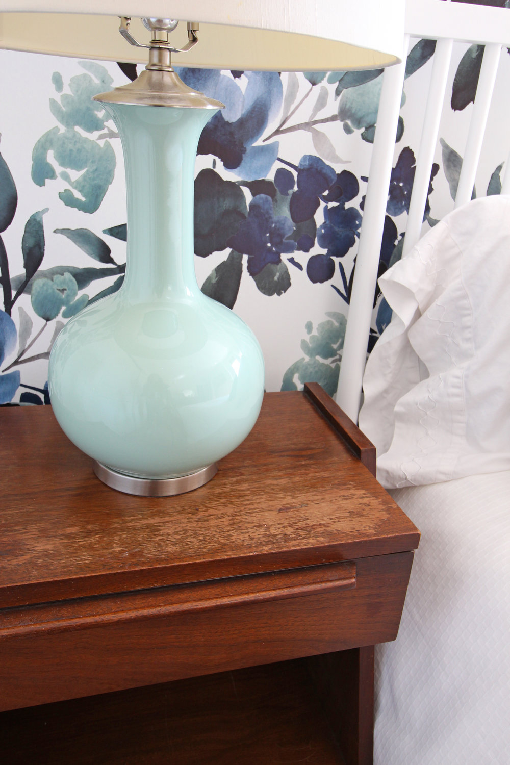 Vintage mid-century nightstand with a blue green lamp.