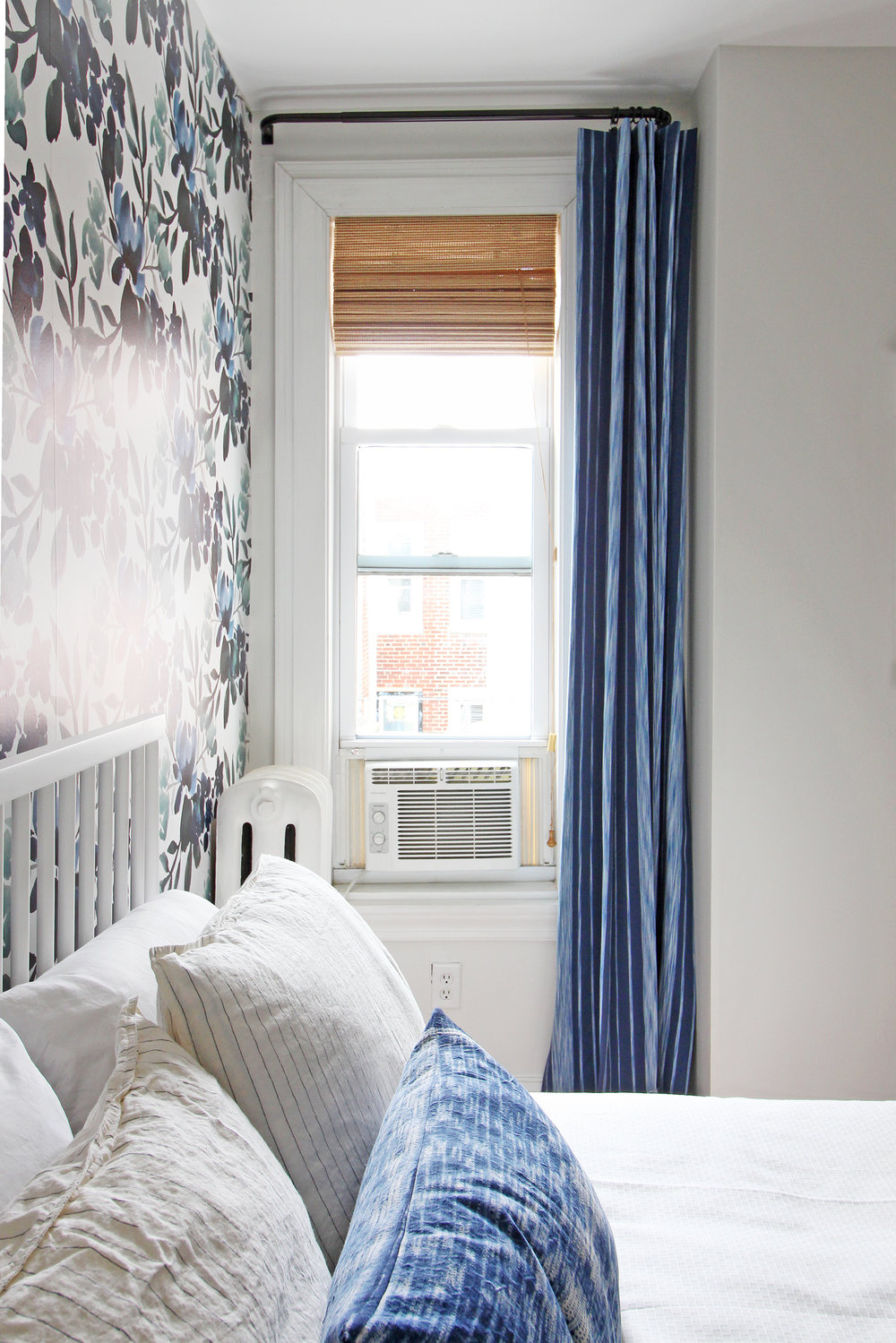 Layered window treatments add beauty and function to a small window in this blue, green, and white guest room!
