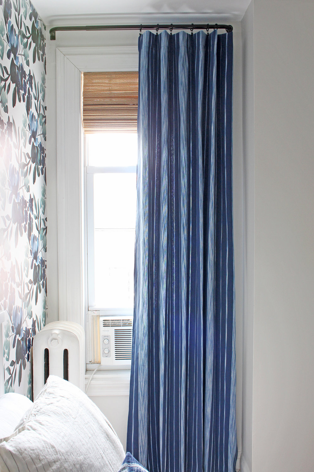 "The beautiful curtain fabric is from Calico (""Pizzelle Navy"" from the new Vern Yip collection). The blue and white stripe is perfectly paired with a woven roman shade and some bold floral wallpaper in this guest room!"
