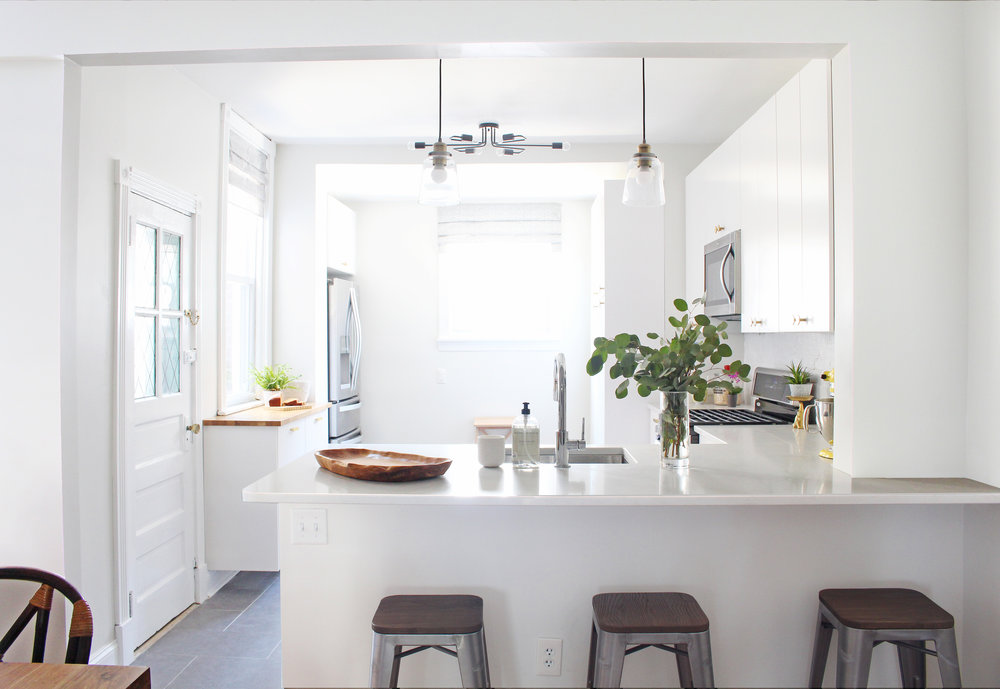 This white and brass kitchen features Caesarstone quartz countertops in London Grey. See the whole house tour over at The Interior Collective! (Design and Photography by Mix & Match Design Company)