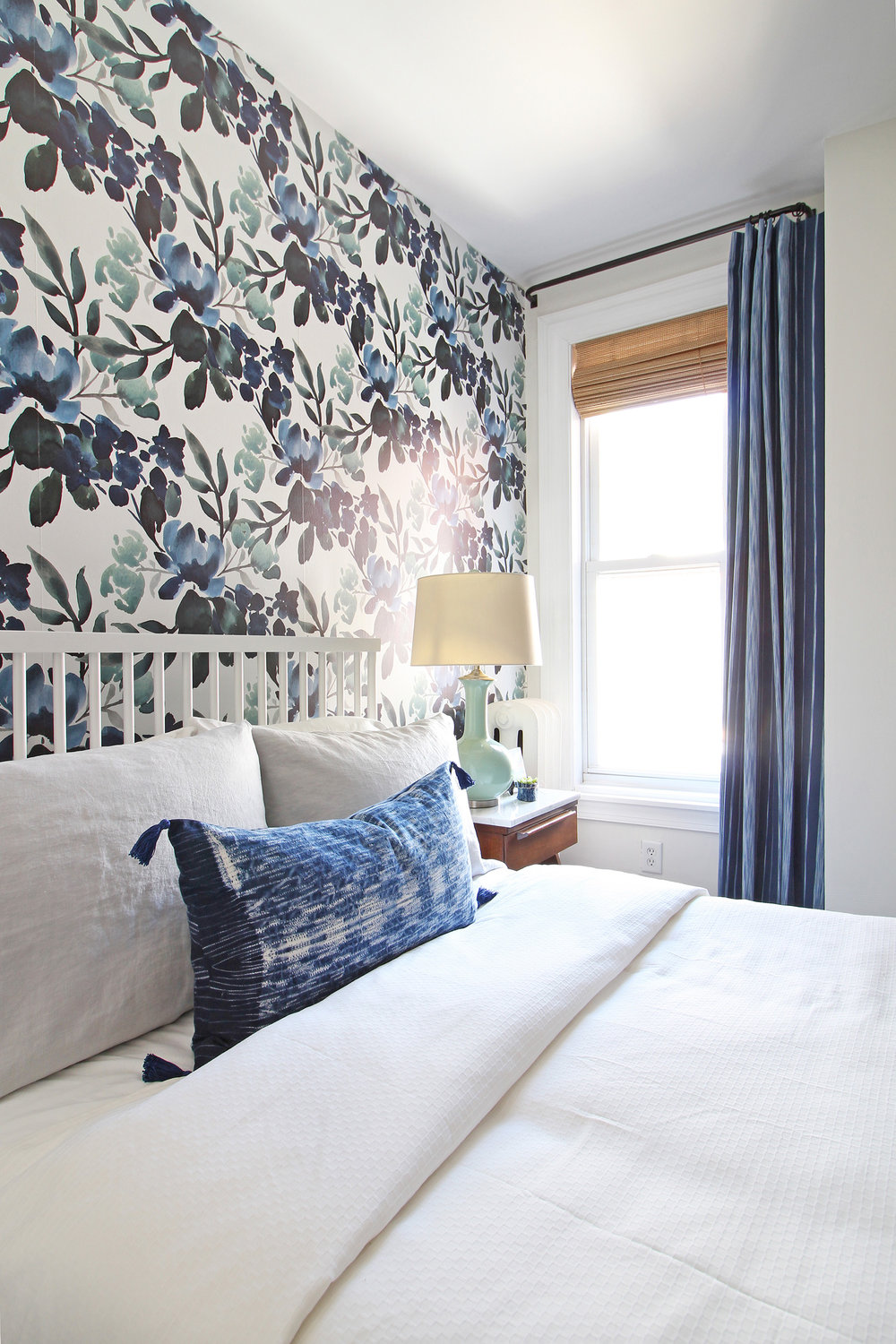 The big One Room Challenge reveal for my eclectic modern farmhouse guest bedroom is up on the blog! Come on over and see the blue-green floral wallpaper, my marble topped vintage nightstands, and my take on modernizing an antique dresser! An indigo lumbar pillow tops off the white bedding. || Design: Mix & Match Design Company