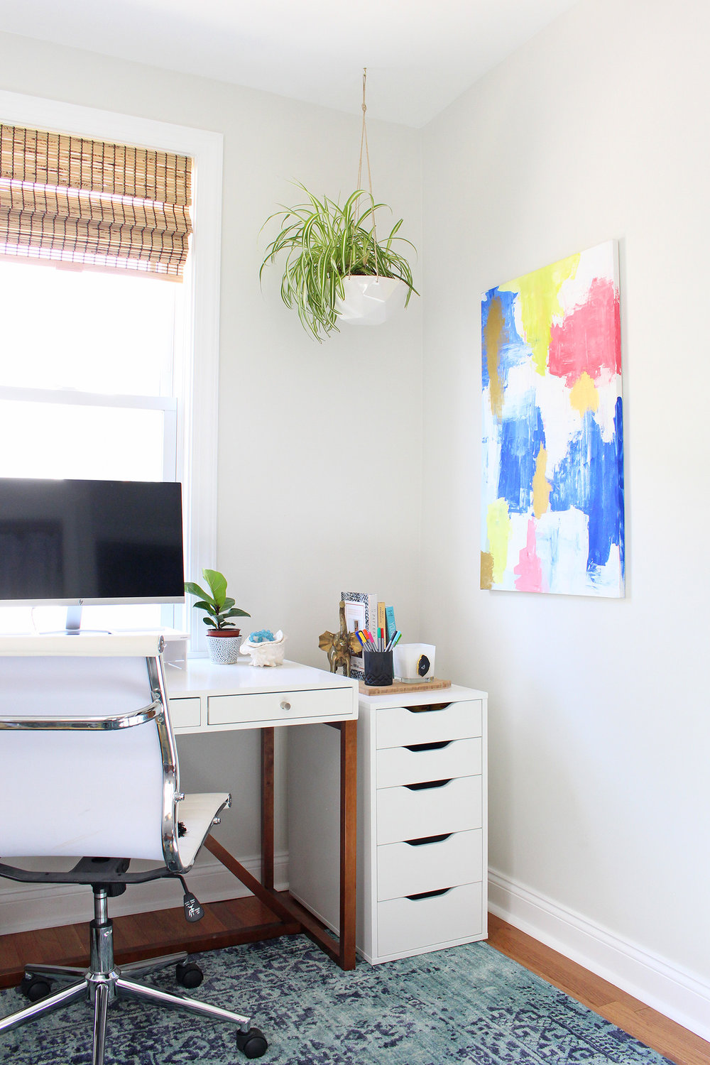 A spider plant hanging in my home office with modern white furniture, an overdyed blue rug, and abstract art. Read more about decorating with houseplants and where to buy them online in this post!
