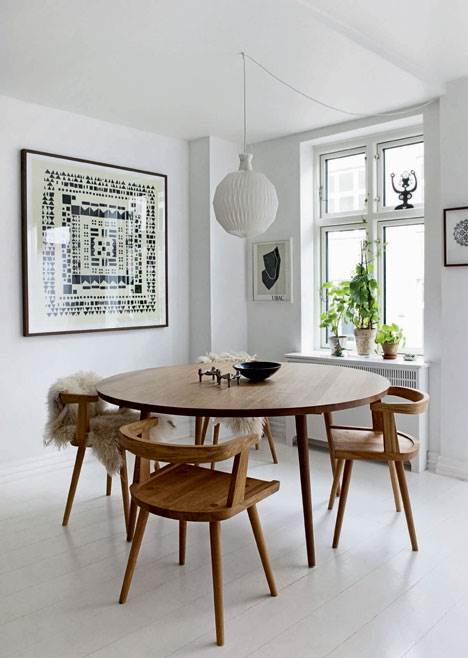 Modern minimalist dining room with wood chairs and a Scandinavian style.