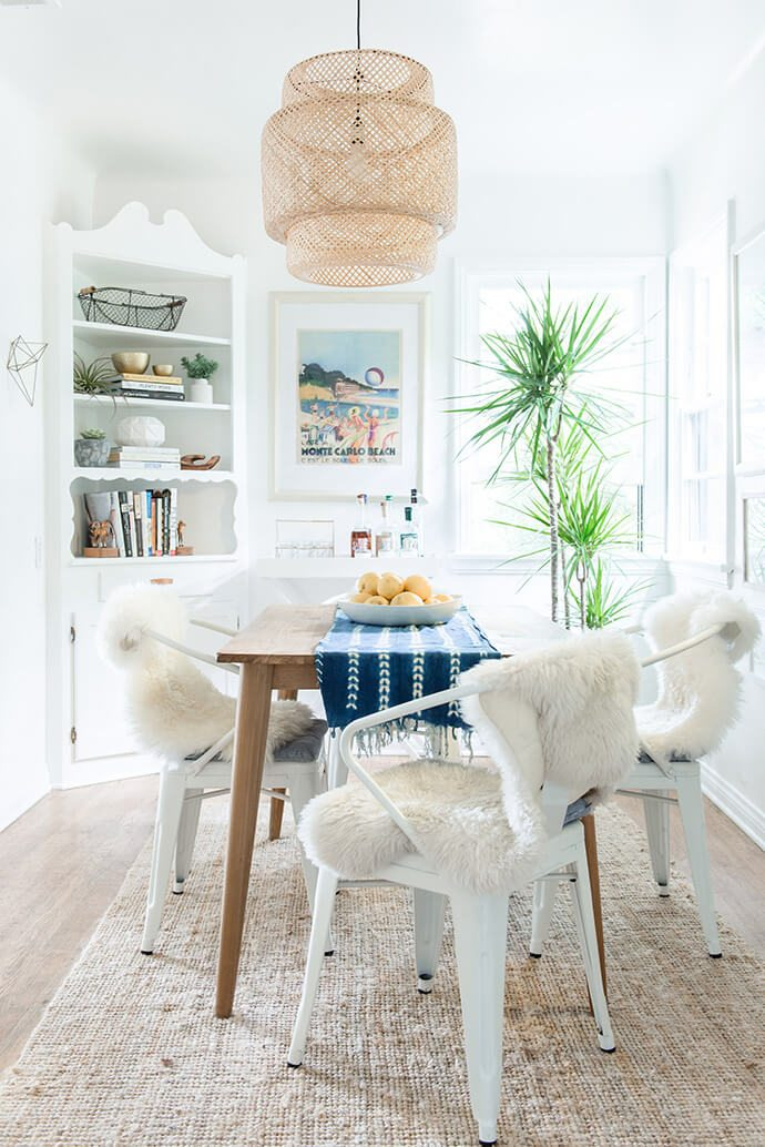 Beachy bohemian dining room with neutral color scheme and a basket pendant light fixture.