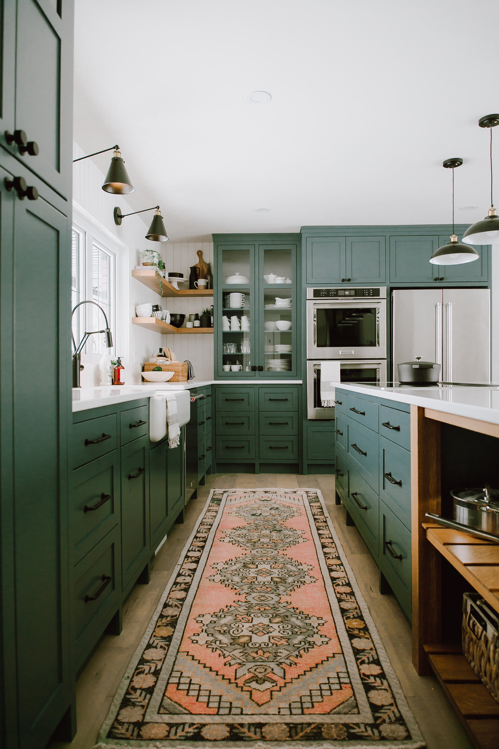 A gorgeous kitchen with dark green cabinets, black hardware, a vintage runner, and open shelving. // Pros and cons of open shelving.