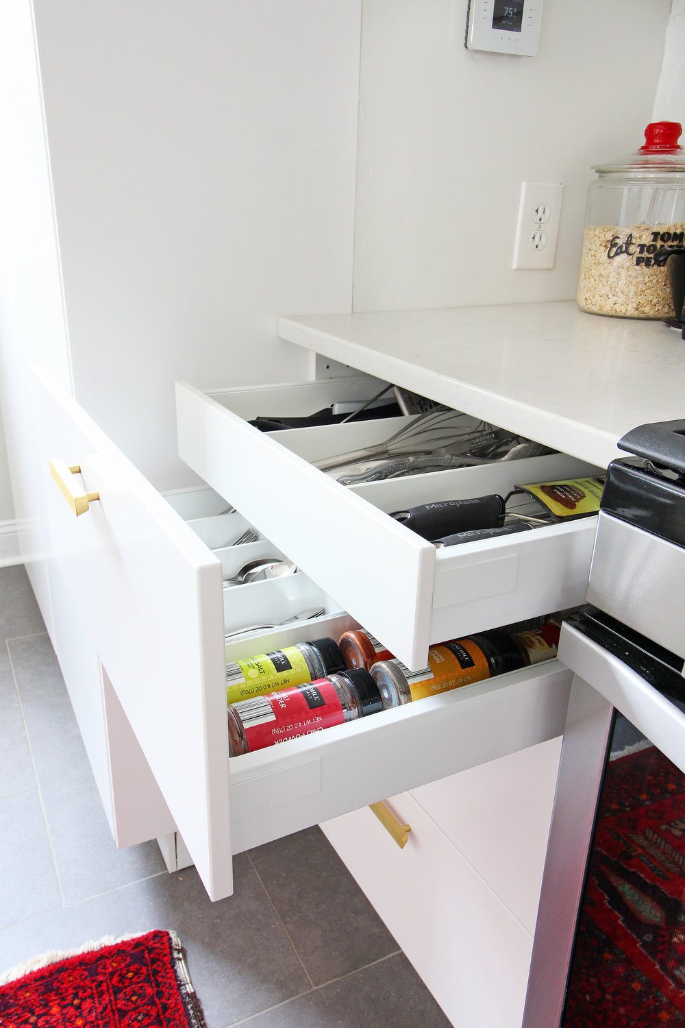 Read my review of our modern white kitchen renovation using IKEA cabinets, Caesarstone countertops, and gray tile floors two years after we renovated. We love the fact that you can customize the interior like this drawer within a drawer!