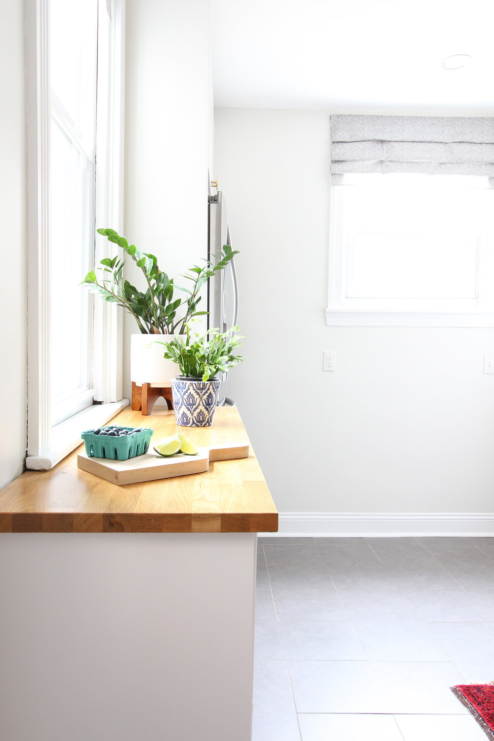 """Read my review of our modern white kitchen renovation using IKEA cabinets, Caesarstone countertops, and gray tile floors two years after we renovated. The butcher block counterotps are on the """"floating cabinets"""" we installed on the far wall of the kitchen."""