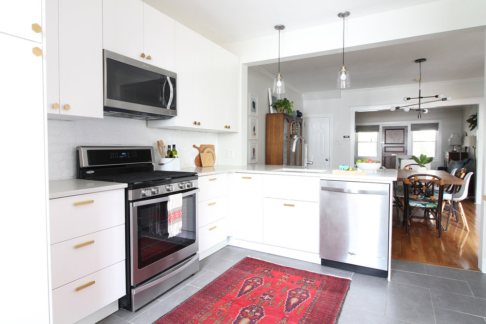 """Read my review of our modern white kitchen renovation using IKEA cabinets, Caesarstone countertops, and gray tile floors two years after we renovated. The brass hardware has been a mix of great and """"eh"""" - come on over to read more about it on the blog!"""