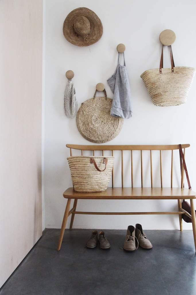 A windsor style bench in this modern entryway, plus the hooks above, makes for a great drop zone and a pretty vignette. For more ideas on how to use benches in your home, click on over to the blog post!