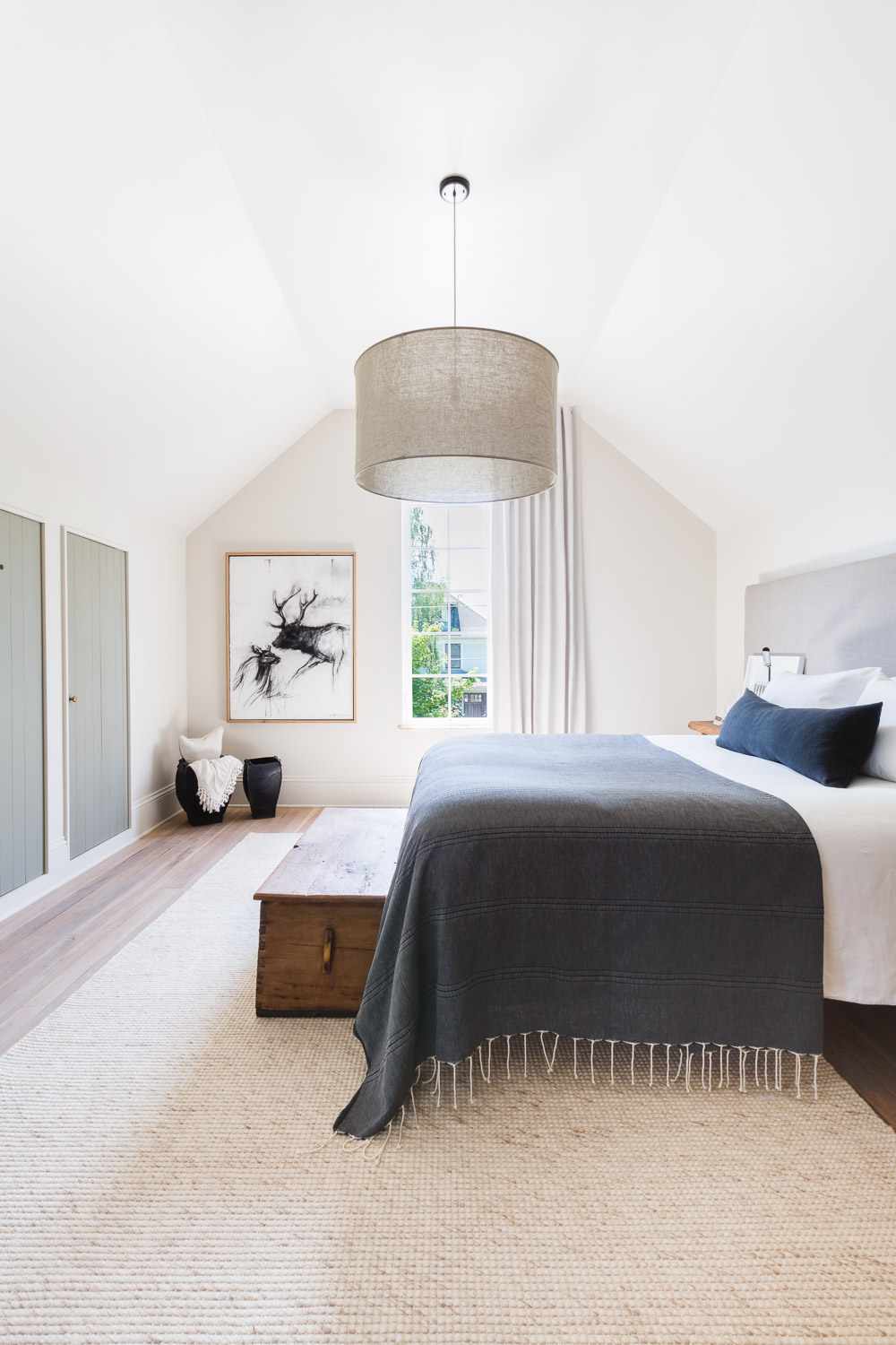This rustic modern bedroom with vaulted ceilings and a bench at the end of the bed is cozy and inviting. For more ideas on how to use benches in your home, head to this blog post!