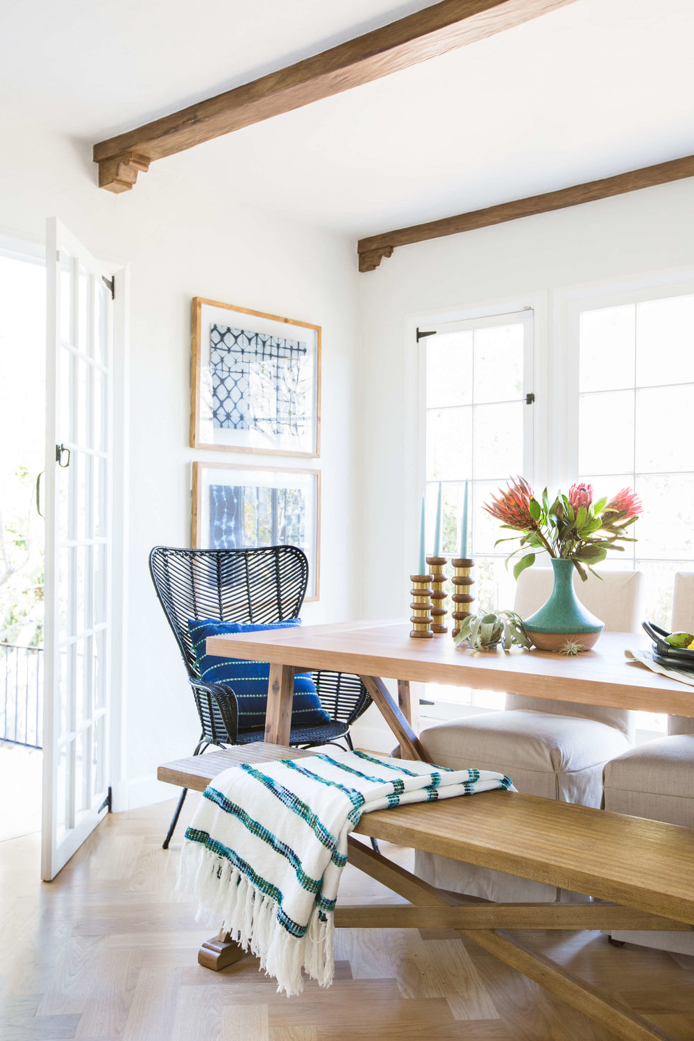 Inspiration for a coastal modern dining room. This blue and white color palette with natural wood feels warm and inviting. I love the dining bench paired with the black rattan chairs. Find out how you can get a similar look in your own home on the blog!