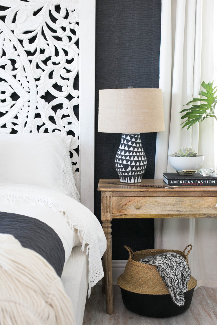 Love the look of this black and white bedroom with a boho eclectic style. The geometric abstract painted table lamp and carved wood headboard are great details. See how you can get a similar look in your own home over on the blog!