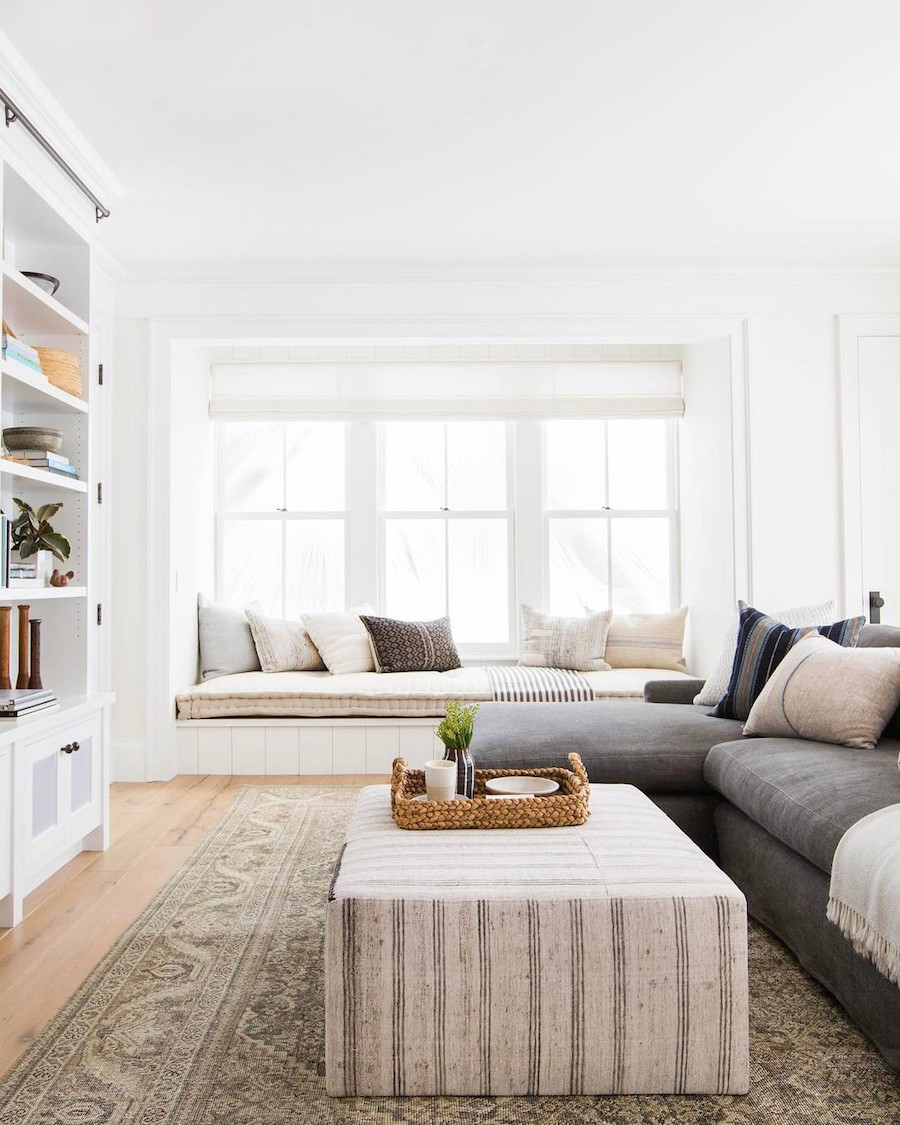 Need help with how to choose a coffee table or ottoman for your living room? I've got you covered! I'll walk you through what you need to think about when you're shopping for one for your home. Plus, I've got a roundup of my favorite coffee tables and ottomans to help you get started in your search. // Modern coastal eclectic living room with striped ottoman and window seat.