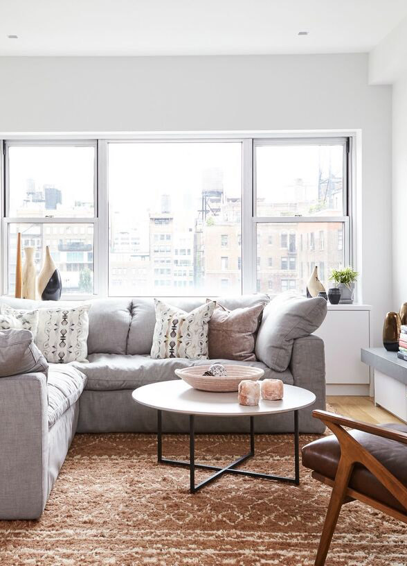 Need help with how to choose a coffee table or ottoman for your living room? I've got you covered! I'll walk you through what you need to think about when you're shopping for one for your home. Plus, I've got a roundup of my favorite coffee tables and ottomans to help you get started in your search. // Modern eclectic living room with sectional and round coffee table.