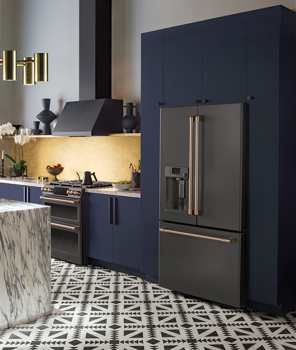 What's your kitchen style? Light and bright, or dark and dramatic? See two examples of these contrasting styles featuring gorgeous matte white and matte black Café Appliances - then weigh in on your favorite! You can find Café Appliances at Gerhard's Appliances if you're local to Philadelphia! // Navy and black kitchen with tribal tile floor and brass hardware