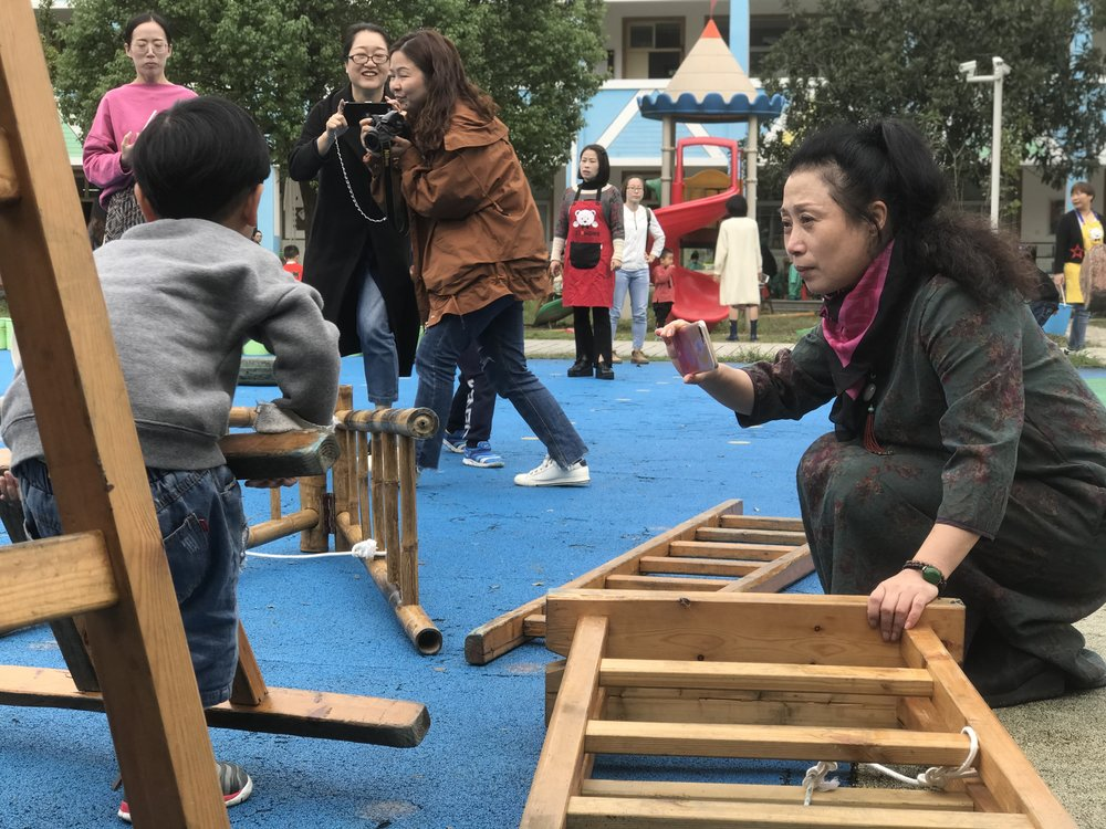 Anji Play founder Cheng Xueqin uses her smartphone to document play.