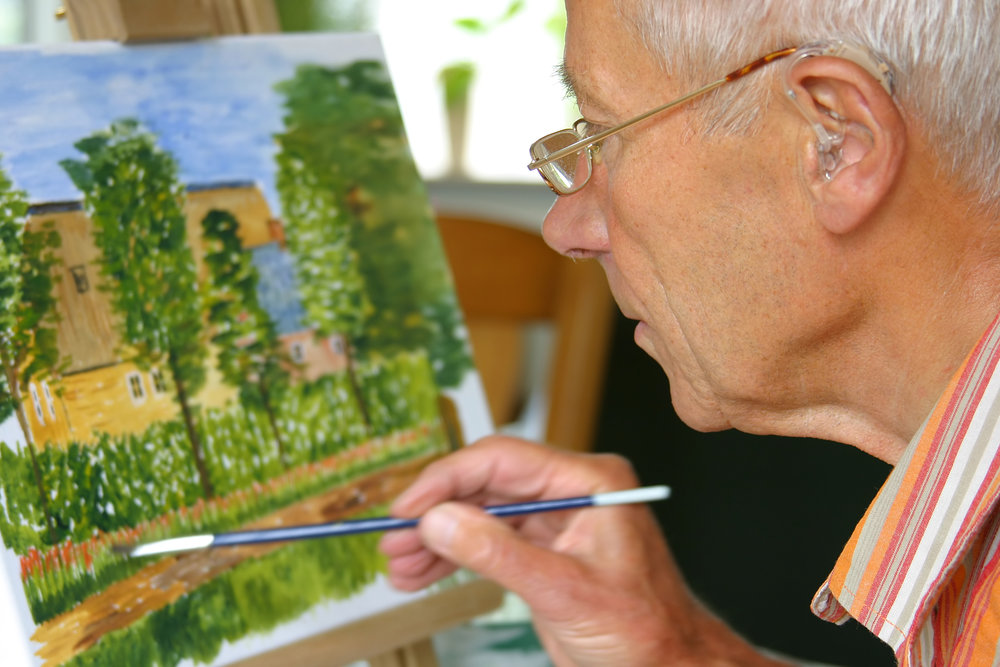 an elderly man painting