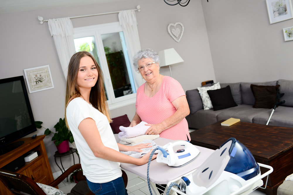 young women helping her elderly mother with ironing