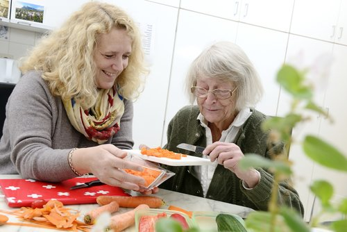 young woman helping her elderly mother cooking