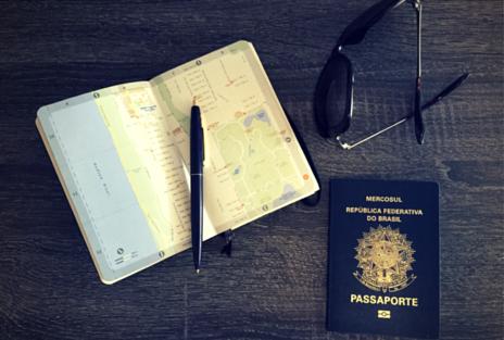 Imagem de um passaporte brasileiro, mapa, caneta e óculos