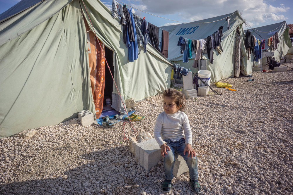A young Syrian girl sits in a refugee camp in Turkey
