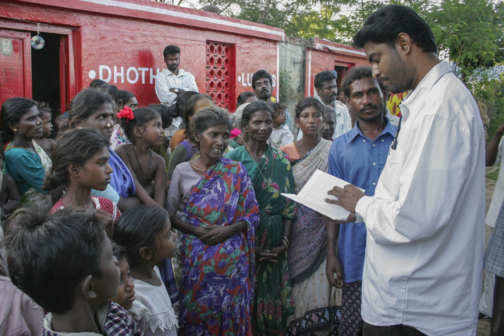 The Rev. A. Sahaya Philomin Raj, S.J., an advocate or lawyer, passes out Tamil translations of the government's guidelines for obtaining tsunami aid in the Dalit village of Yerum Salai Graman, in southeast India. The government had published the guidelines in English, which the Jesuits then translated.